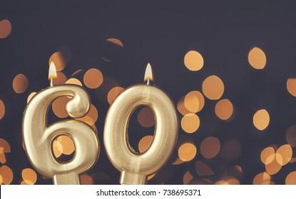 Gold number 60 celebration candle against blurred light background