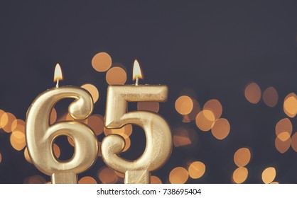 Gold number 65 celebration candle against blurred light background