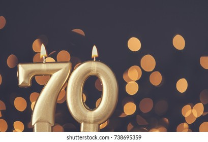 70th Birthday Cards Gold Number 70 Celebration Candle Against Blurred Light Background