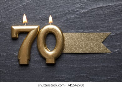 Gold number 70 celebration candle with glitter label