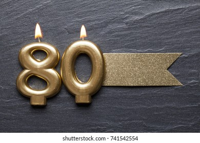 Gold number 80 celebration candle with glitter label