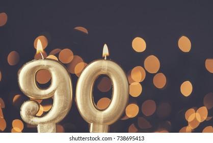 Gold number 90 celebration candle against blurred light background