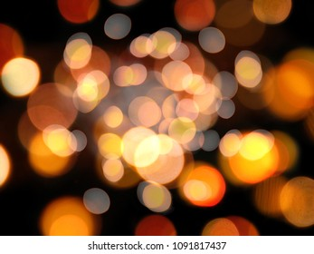 Gold and orange expanding round blurred lights abstract on a black night background