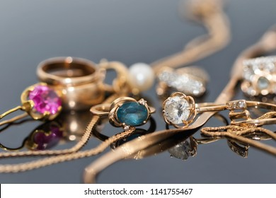 Gold ornaments in different shapes and with different stones lie together on a reflective surface