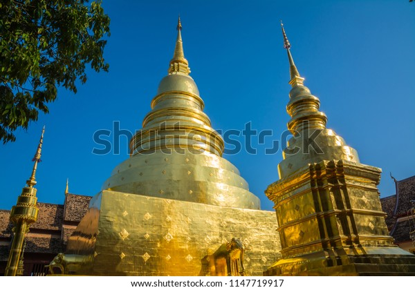 Gold pagoda at Phra Singh temple, Chiang Mai, Thailand with blue sky in the background