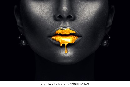 Gold Paint drips from the lips, lipgloss dripping from sexy lips, golden liquid drops on beautiful model girl's mouth, black skin. Make-up. Beauty dark face makeup close up, isolated on black