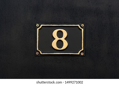 Gold painted house number 8 on a black number shield