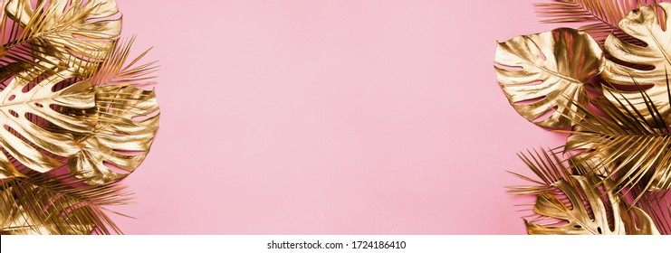 Gold painted tropical date palm and monstera leaves border frame on pastel pink abstract background isolated. Room for text. Beauty fashion banner template.