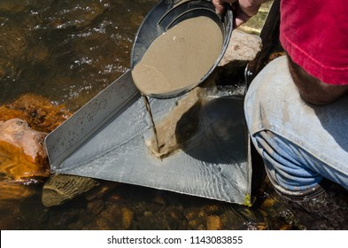 Gold panning with sluice box. Gold prospector feeding mineral rich material into sluice box. Fun recreational outdoor activity of gold panning and gem stone mining.
