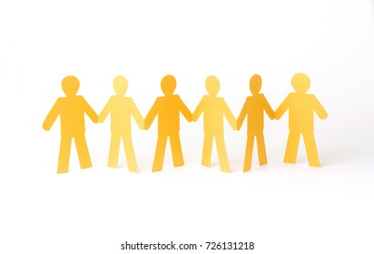 gold paper cut people standing holding hands, stacks on a white background, Concept collaborative, teamwork business.
