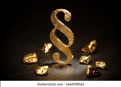 Gold paragraph sign and gold nuggets on black background.