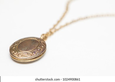 Gold pendant locket necklace on a white background shot up close