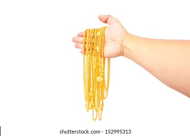 gold pendants in hand on white background