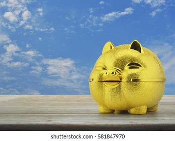 Gold piggy bank on wooden table over blue sky with white clouds, Saving money concept