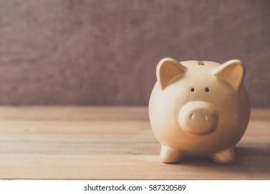 Gold Piggy bank on wooden table background