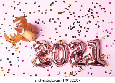 Gold pink balloons in form of numbers 2021. Colorful shiny confetti and christmas bauble deer on pink background. Happy New Year celebration. Flat lay, top view