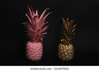 Gold and pink painted fresh pineapples on black background