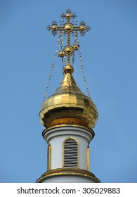 Gold plated dome with a cross in the Orthodox Cathedral on blue sky background