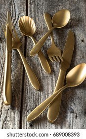 Gold plated flatware on rustic background