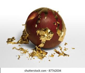 gold plated peach peeling away golden flakes, studio shot in light back