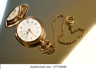 Gold pocket watch on gold glass background close-up