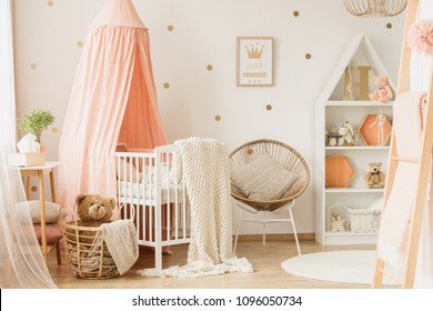 Gold poster on the wall in child's bedroom interior with armchair next to pink cradle with knit blanket