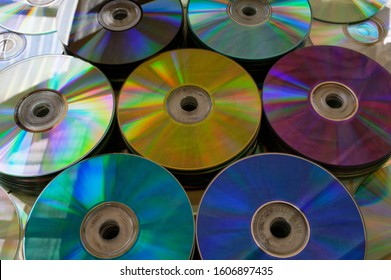 Gold, purple, blue, black and teal DVDs in stacks