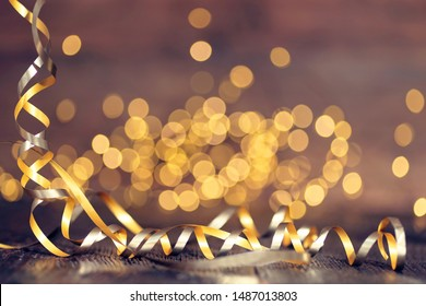 Gold rays of light with bubbles and glitters on wooden background