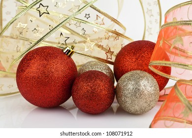 Gold and red Christmas baubles with gold and red ribbon.