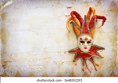 Gold and red elegant traditional Venetian jester mask over distressed old white wooden background