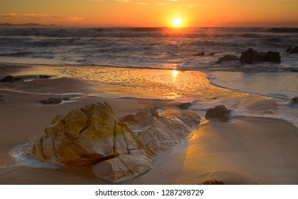 Gold and red sunrise light reflects from a gentle sea and wet sand and the water's edge. A boulder nudges into the water, patterned with beautiful dawn colours.