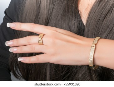 gold ring and bracelet set on a hand with French manicure