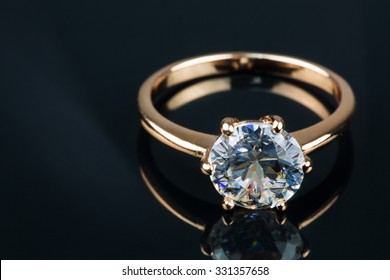 Gold ring with brilliant isolated on black background