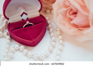 Gold ring with diamond in the red heart box with pink roses on white background