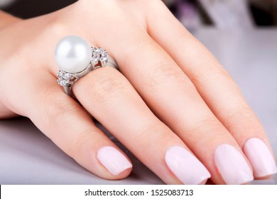 Gold ring with diamonds and pearl. Beautiful female hands with diamond ring with pearl. Diamond ring with pearl. Woman's nails with manicure. White gold.