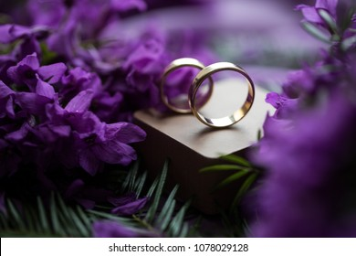 Gold ring. Jewellery. Gold expencive ring. Macro image of spring lilac violet flowers, abstract soft floral background