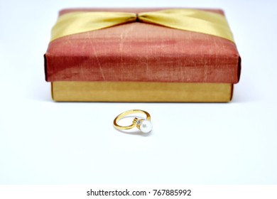 Gold ring with pearl and diamond on top in front of red and golden gift box on white isolated (Selective focus)