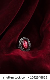 gold ring with red stone on red velvet