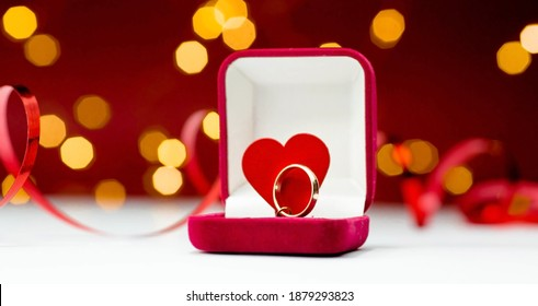 Gold ring, wedding ring in red box and, red heart on white-red background with beautiful bokeh. The moment of a wedding, anniversary, engagement, or Valentine's Day. Happy day.