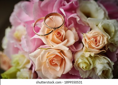 gold rings and a beautiful bridal bouquet of roses on the background. details, wedding traditions. close-up, macro