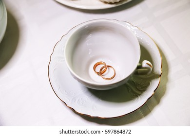 Gold rings newlyweds and empty white Cup