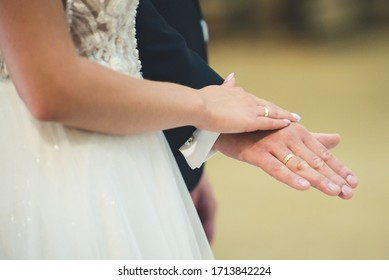 gold rings on the fingers of the newlyweds