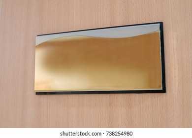 gold room name label on wood door