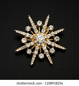gold round brooch with diamonds isolated on black