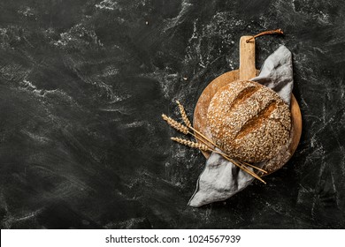 Gold round loaf of rustic bread and ears of wheat on wooden board captured from above (top view, flat lay). Black chalkboard background. Layout with free copy (text) space.