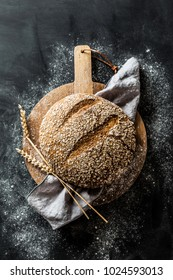 Gold round loaf of rustic bread and ears of wheat on wooden board captured from above (top view, flat lay). Black chalkboard as background. Dark moody light.
