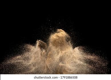 Goldene Sandexplosion einzeln auf schwarzem Hintergrund. Abstrakte Sandwolke.