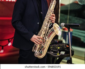 Gold saxophone with specks on it in male hands in the red background