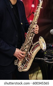 Gold saxophone with specks on it in male hands in the red background.Hands of musician playing alto saxophone, closeup,Hands of groom play on saxophone,jazz music concept