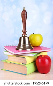 Gold school bell with school supplies on table on bright background